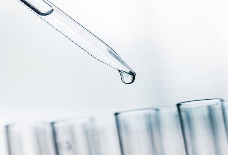 Lab. A close-up of a laboratory glass pipette with emerging drop of substance over one of several test tubes on a light  background